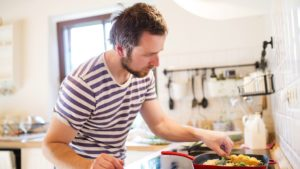 man in stripes cooking
